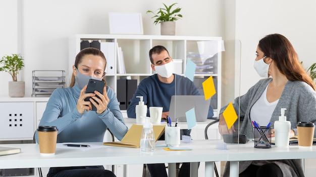 중간 샷 사람들이 책상에 앉아