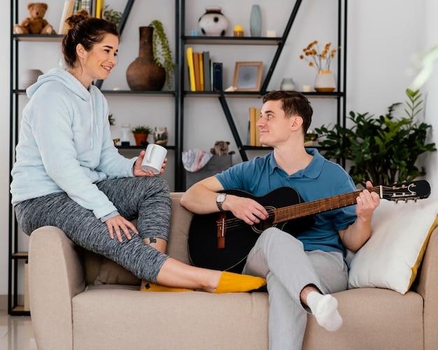 ソファにギターを持っているミディアムショットの人々