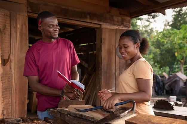 木材を扱うミディアムショットの人々