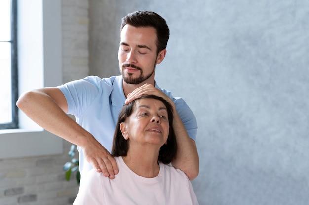 여자를 돕는 중간 샷 물리 치료사