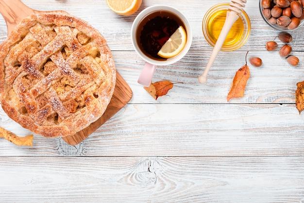 Medium shot of pie with tea and honey