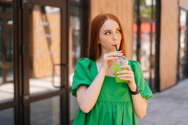 Medium shot portrait of cheerful attractive young woman holding cool cocktail standing at city street in sunny summer day, looking away. pretty lady drinking cold beverage through straw.