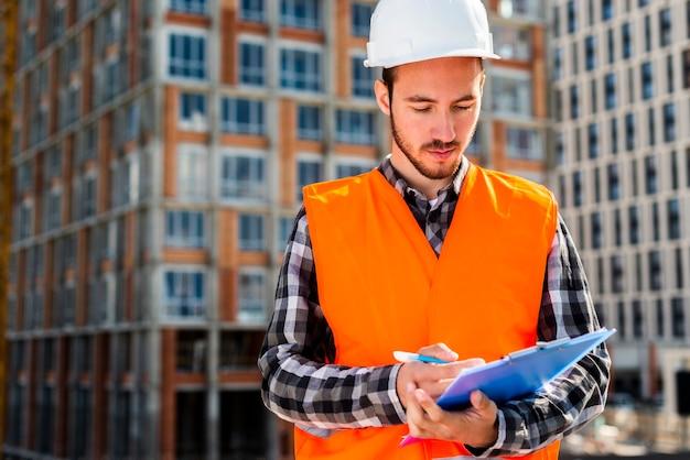 Medium shot portrait of construction engineer holding clipboard