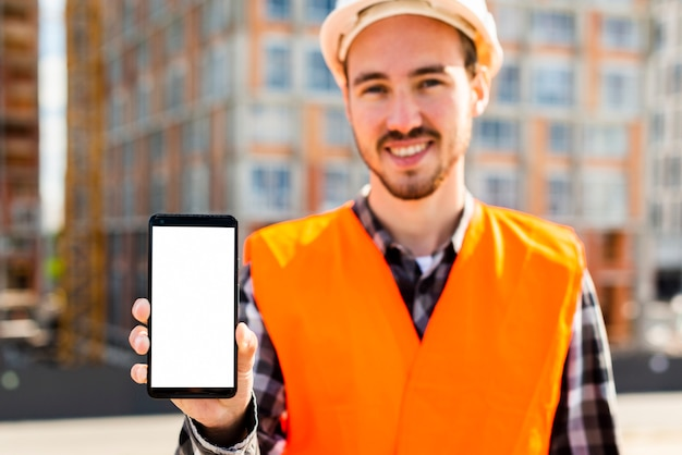 Medium shot portrait of construction engineer holding phone