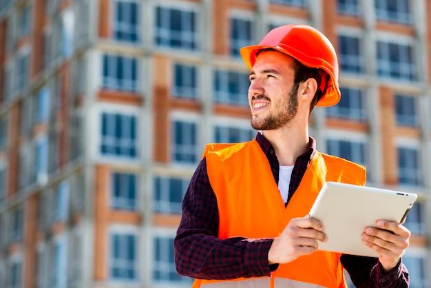 Medium shot portrait of construction engineer holding tablet