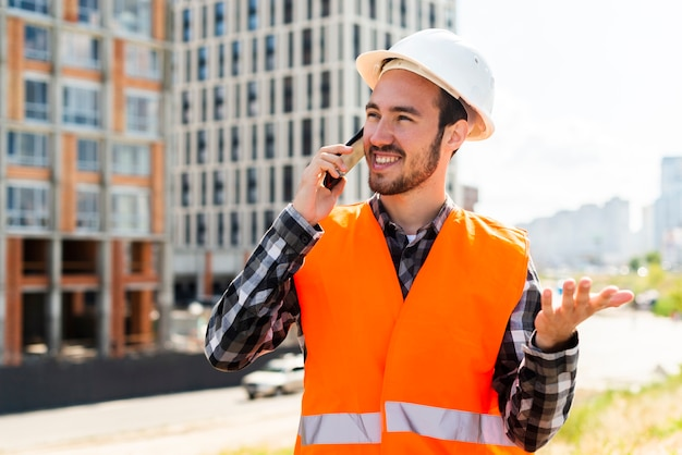 Medium shot portrait of construction engineer talking on the phone