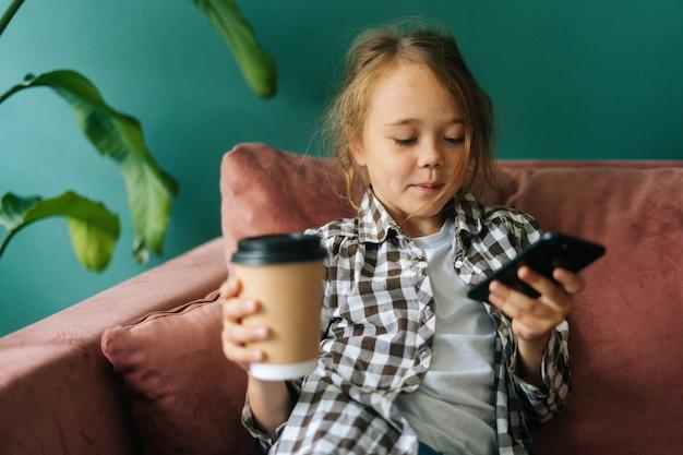 Средний снимок портрета очаровательной милой маленькой девочки, использующей смартфон, смотрящей на экран