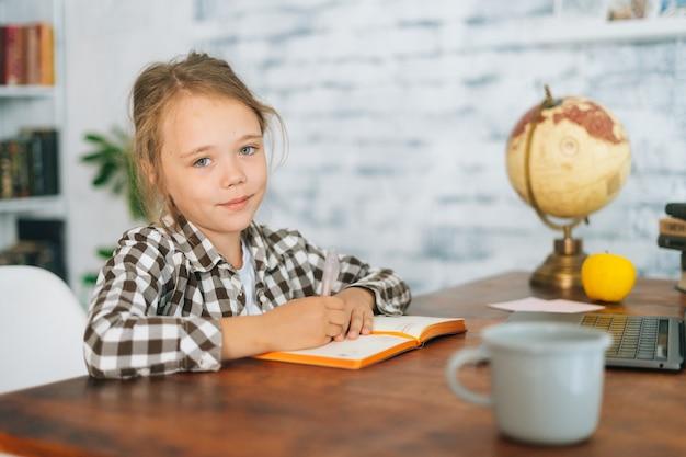 Средний снимок портрет улыбающейся симпатичной школьницы младшего возраста, делающей домашнее задание, сидя за столом с ноутбуком и бумажной записной книжкой у себя дома. очаровательные школьницы начальных классов электронного обучения онлайн.