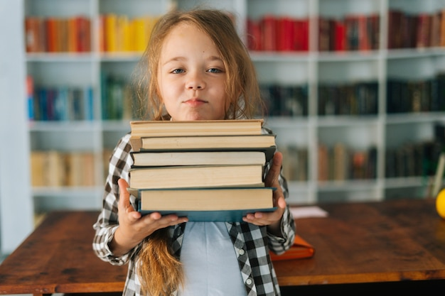 Medium shot portrait of pretty elementary child school girl holding stack of books in library at