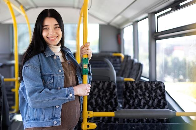 Medium shot pregnant woman on bus