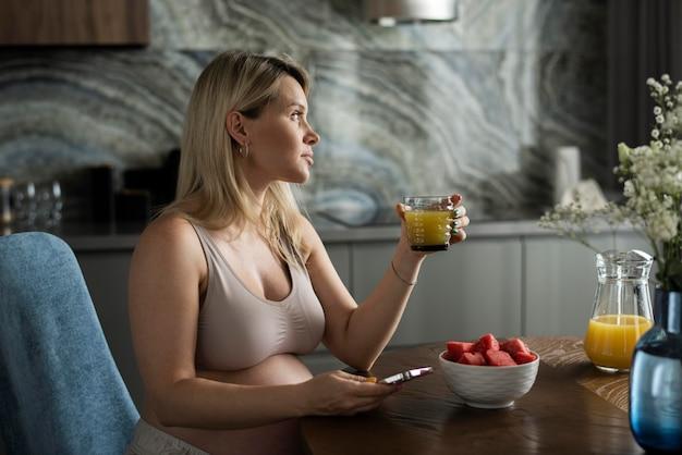 Donna incinta a colpo medio con succo