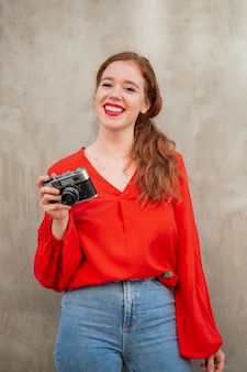 Medium-shot redhead woman using a vintage camera