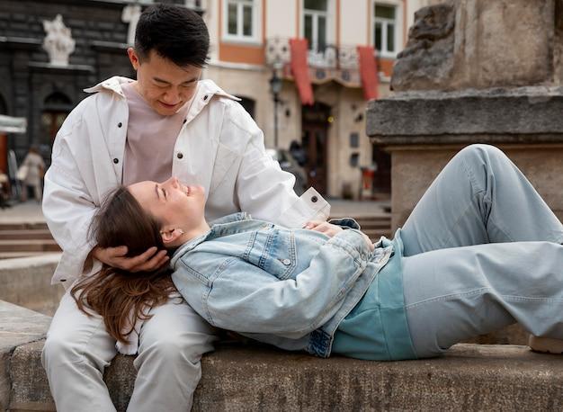 屋外に座っているミディアムショットのロマンチックなカップル