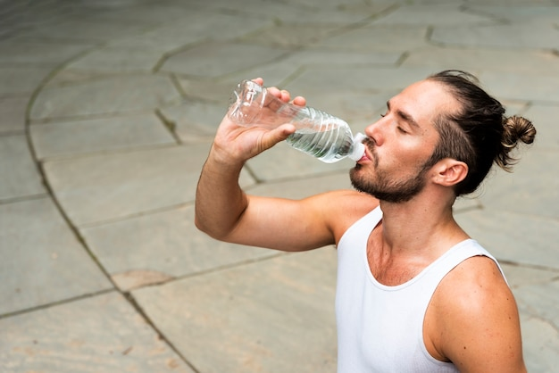 Medium shot of runner drinking water
