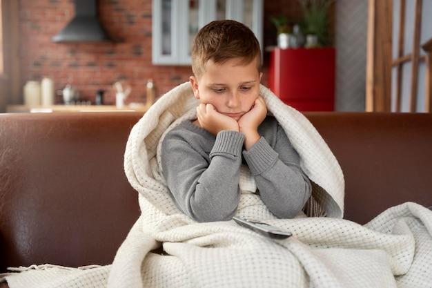 Средний снимок грустного ребенка, сидящего на диване