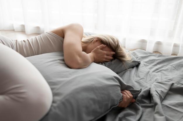 침대에서 중간 샷 슬픈 여자