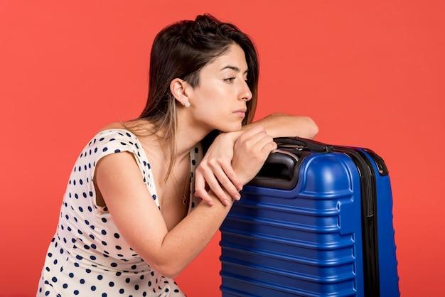 Donna triste del colpo medio con bagagli