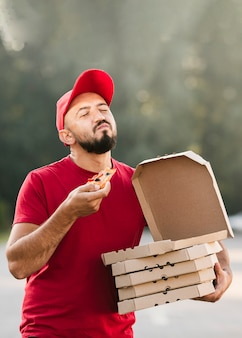 Medium shot satisfied delivery guy eating pizza