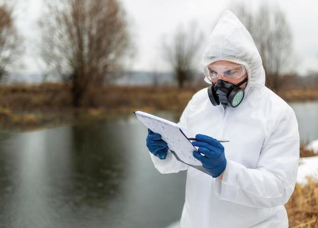防護服を着たミディアムショットの科学者