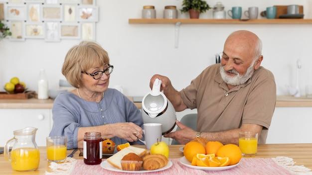 テーブルでミディアムショットの年配のカップル
