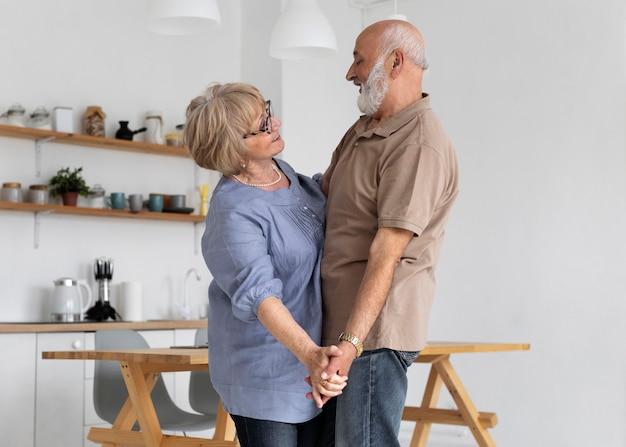 Средний снимок старшей пары, танцующей вместе