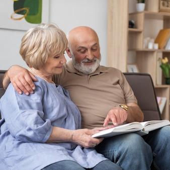 Medium shot senior couple holding book