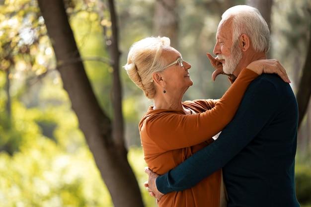 Medium shot senior couple holding each other