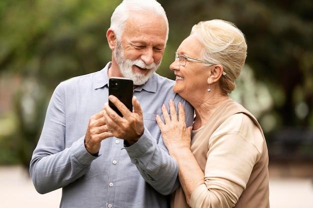 電話を保持しているミディアムショットの年配のカップル