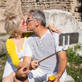 ミディアムショットの年配のカップルがキス