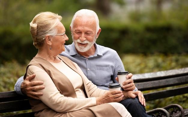 カップとベンチでミディアムショットの年配のカップル