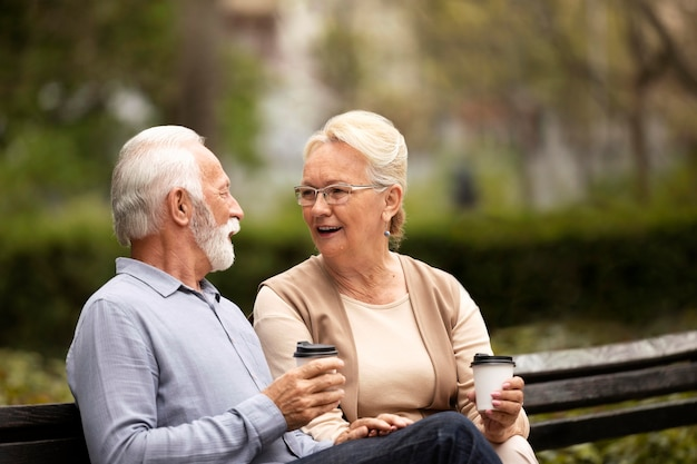 ベンチでミディアムショットの年配のカップル