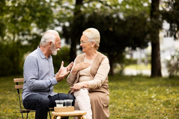 椅子にミディアムショットの年配のカップル
