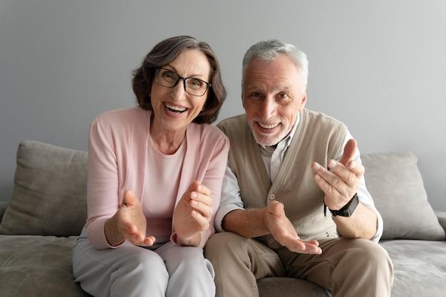 ソファの上のミディアムショットの年配のカップル
