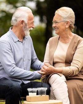 外のミディアムショットの年配のカップル
