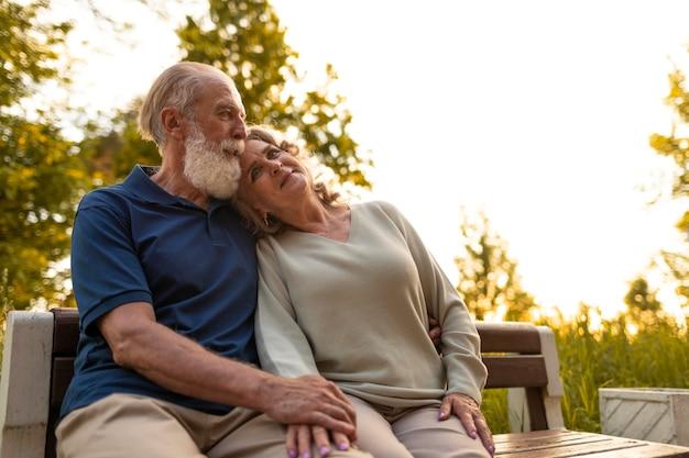 ベンチに座っているミディアムショットの年配のカップル