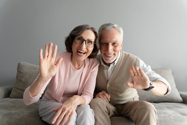 手を振っているミディアムショットの年配のカップル
