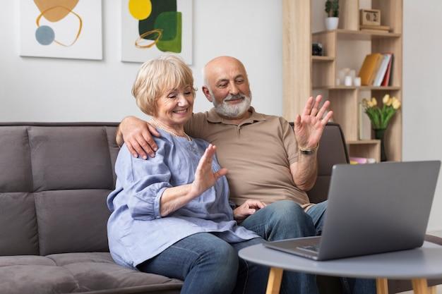 Medium shot senior couple with device