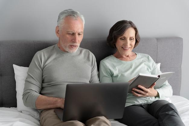 デバイスとミディアムショットの年配のカップル