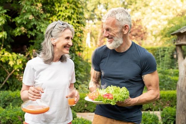 食べ物とミディアムショットの年配のカップル