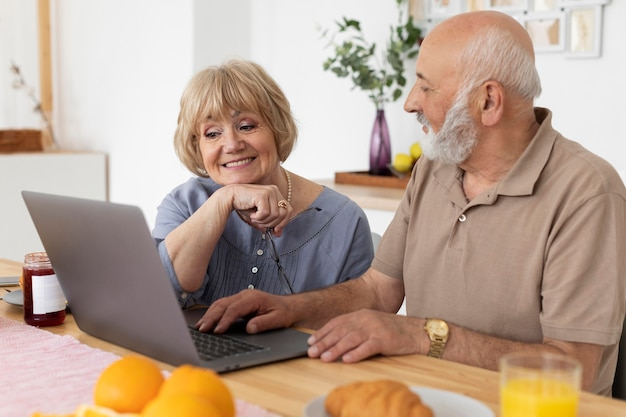 Coppia senior del colpo medio con il computer portatile