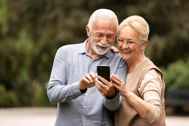 Пожилая пара среднего выстрела с телефоном
