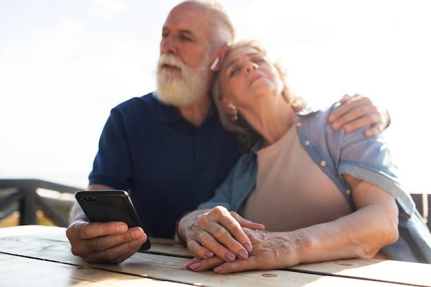 電話でミディアムショットの年配のカップル
