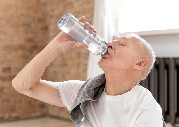 ミディアムショットの年配の男性が水を飲む