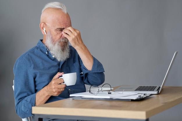 Medium shot senior man experiencing headache