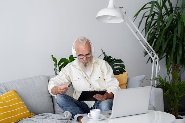 Uomo anziano a tiro medio che impara con il computer portatile