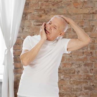 Средний выстрел старший мужчина растягивается в помещении