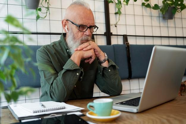 Uomo anziano a tiro medio che studia con il computer portatile