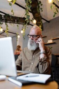 電話で話しているミディアムショットの年配の男性
