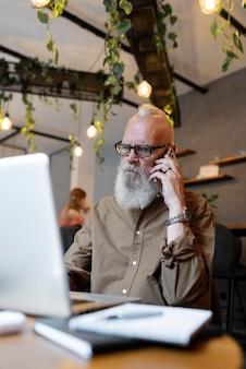 Uomo anziano a tiro medio che parla al telefono