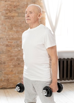 Medium shot senior man with dumbbells